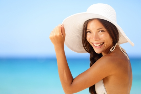 asian bikini: Vacation beach woman smiling happy portrait. Asian bikini girl on tropical beach wearing sun hat looking at camera happy. Summer lifestyle photo with mixed race Asian Caucasian female model.
