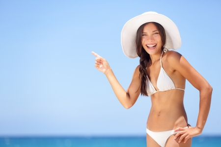 Beach woman pointing showing vacation concept. Beautiful happy summer bikini girl on tropical beach holidays travel pointing happy smiling at copy space. Attractive multiracial Asian Caucasian model. photo