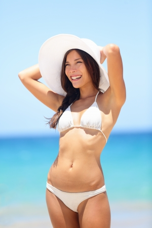 Happy beach woman enjoying summer sun with tropical sea in background. Summer vacation holidays travel concept with beautiful mixed race Asian Caucasian bikini model outside. photo