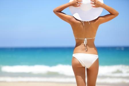 Vacaciones en la playa. Hermosa mujer caliente en bikini y sunhat de pie con los brazos levantados en la cabeza disfrutando de la vista de aspecto de la playa del océano en un día caluroso de verano. Foto de la playa de Hapuna, isla grande, Hawaii. Foto de archivo