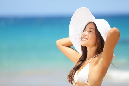 beach hat: Relaxing beach woman enjoying the summer sun happy standing in a wide sun hat at the beach with face raised to the sunlight. Head and shoulder portrait. Multicultural Asian Caucasian in enjoyment. Stock Photo