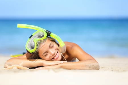 scuba goggles: Travel summer vacation beach woman with snorkel. Smiling beautiful young woman relaxing lying on white beach sand in the summer sun with a blue ocean. Photo from Hapuna beach, Big Island, Hawaii, USA. Stock Photo