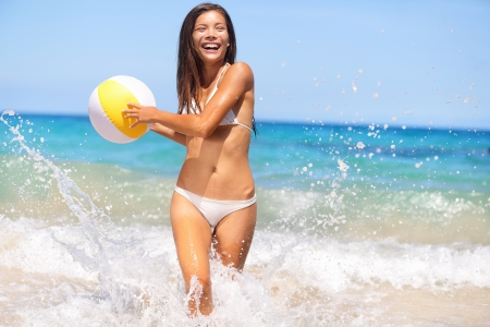 splash mixed: Beach woman having fun laughing enjoying sun in bikini running at with water spray splashing and a beach ball in her hands laughing happy. Beautiful joyful cheerful multiracial asian caucasian girl. Stock Photo
