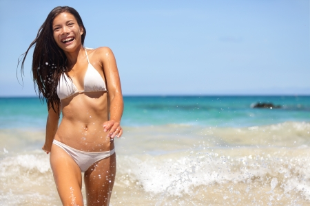People having summer beach fun - woman in water smiling happy walking towards camera. Bikini girl on summer travel vacation on Hapuna beach, Big Island, Hawaii, USA. Multiracial Asian Caucasian woman. photo