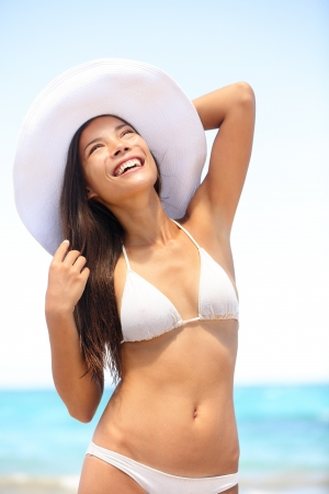 Sexy happy young woman at the beach wearing white sun hat and bikini bathing suit at the tropical ocean. Beautiful multiracial Asian Caucasian female model outside on summer travel. photo