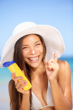 sun protection: Sunscreen woman applying suntan lotion laughing. Beautiful vivacious laughing woman in a sunhat and bikini applying suntan cream from a plastic container to her nose with ocean in background. Stock Photo
