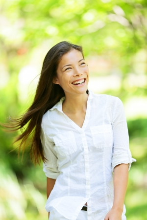 verve: Joyful vivacious woman in a spring or summer park beaming a broad smile as she walks along rejoicing in the freshness of nature and the warm glow of the sunlight through the leaves of the green trees Stock Photo