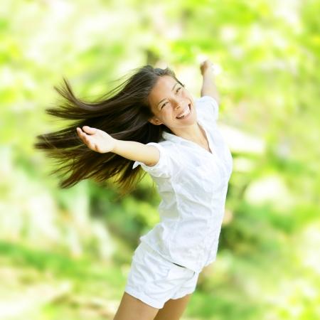 Verheuging gelukkige vrouw in vliegende beweging lacht vol vreugde en vitaliteit in de zomer of het voorjaar van bos. Eurasian vrouwelijk model. Stockfoto