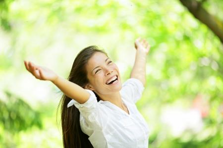 Zorgeloos opgetogen gejuich vrouw in de lente of de zomer bos park vol hoop en vitaliteit. Multiraciale meisje verhogen haar armen omhoog glimlachen gelukkig. Gemengd ras Aziatische Kaukasische vrouwelijke model.