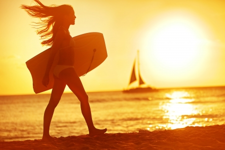 Summer woman body surfer beach fun at sunset. Body surfing girl walking in sunshine in warm evening sun with body surfboard. Water sport summer vacation travel concept. Kaanapali beach, Maui, Hawaii, USA photo
