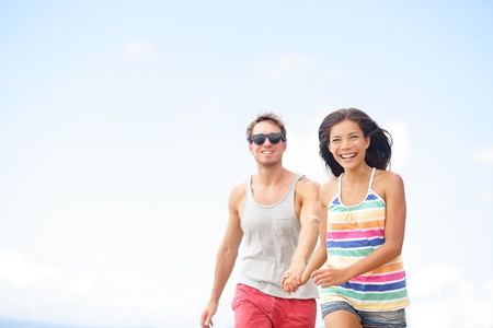 Couple having fun laughing in love outside running together holding hands. Joyful happy happiness lifestyle image with interracial young couple in their twenties, Asian woman, Caucasian man. photo