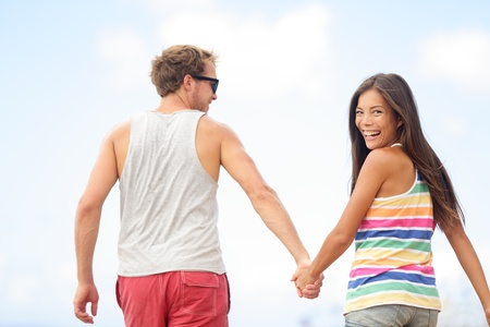 Happy cheerful young trendy couple holding hands walking together outside smiling having fun being in love. Beautiful young multiethnic couple, Asian woman, Caucasian man. Stock Photo - 19203328