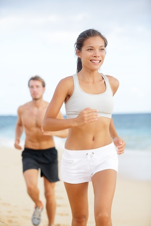 Running couple. Woman fitness runner smiling happy during jogging exercise outside on beach with male fitness sport model. Multiracial couple, Asian female model and Caucasian man exercising together. photo