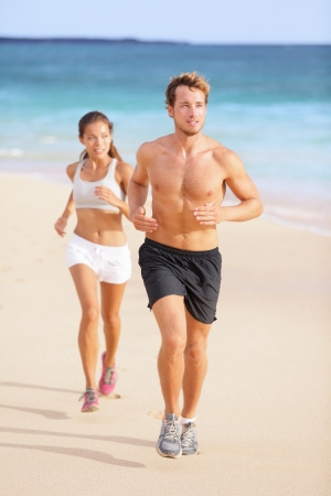 Couple running - man fitness runner first. Runners in jogging exercise outside on beach. Multiracial couple, Asian woman model and Caucasian male fitness sport model exercising together. Stock Photo
