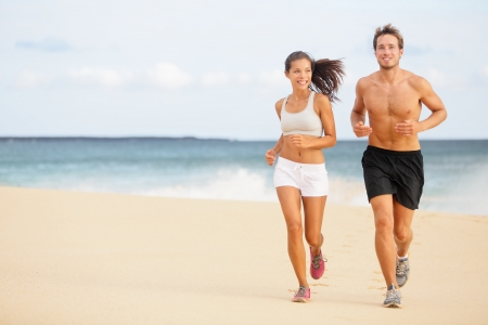 active: Runners. Young couple running on beach. Athletic attractive people jogging in summer sport shorts enjoying the sun exercising their healthy lifestyle. Multiethnic couple, Asian woman, Caucasian man.