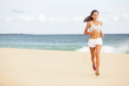 Running woman jogging on beach. Female runner training outside in summer. Fit young female sport fitness model exercising in full body. Beautiful fit Asian Caucasian woman in her twenties. photo