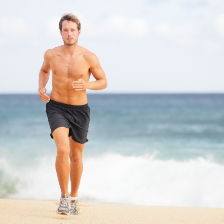 Running man jogging on beach. Male runner training outside working out. Fit young male sport fitness model exercising in full body in summer. Handsome strong caucasian man in his twenties. Stock Photo - 19226462