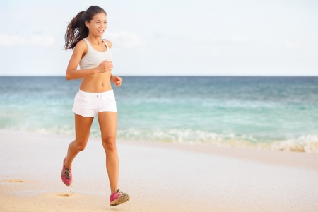 Woman runner jogging or running on beach training in barefoot sport shoes. Beautiful young fit fitness model in working out outside in summer wearing shorts. Mixed race Asian / Caucasian female girl Stock Photo - 19226466