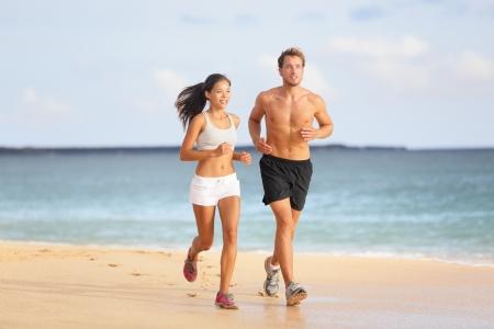 hacer footing: Gente corriendo - joven pareja trotar en la playa. Atractivo ajuste deportivo joven pareja corredores al lado del otro en la playa bajo el sol de verano, disfrutando del aire fresco mientras se entrenan juntos