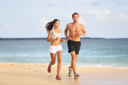 People running - young couple jogging on beach. Attractive fit sporty young couple runners side by side on the beach in the summer sunshine enjoying the fresh air as they train together photo