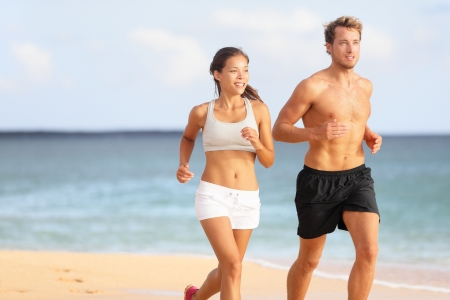 Couple running. Sport runners jogging on beach working out smiling happy. Fit male fitness model and attractive female jogger. Multiracial group, Asian woman and Caucasian man. Stock Photo