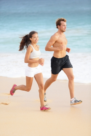 Running couple jogging on beach. Runners sport training together outside on beautiful beach. Fit athlete fitness model man and attractive woman. Multiracial, Asian female and Caucasian male runner. photo