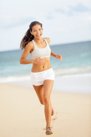 fitness model: Runner woman running on beach smiling happy. Beautiful vivacious woman jogging on the beach in summer sport shorts laughing as she enjoys the exercise and sunshine. Asian fitness model exercising.