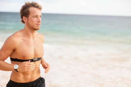 Runner man running with heart rate monitor on beach topless. Fit titness athlete model jogging training for marathon run outside. Young male caucasian in his twenties photo