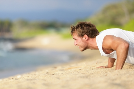 push ups: Sit-ups - man fitness model training on beach outdoors. Fit male fitness trainer working out exercising in summer on beach.