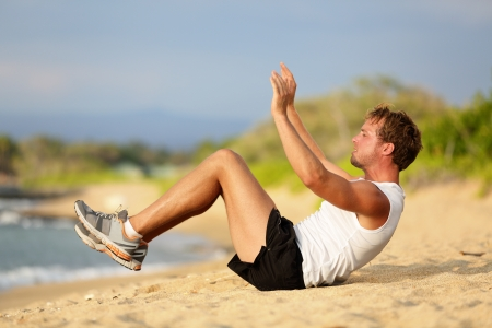 situps: Fit male fitness model in intense workout session on beach outside. Stock Photo