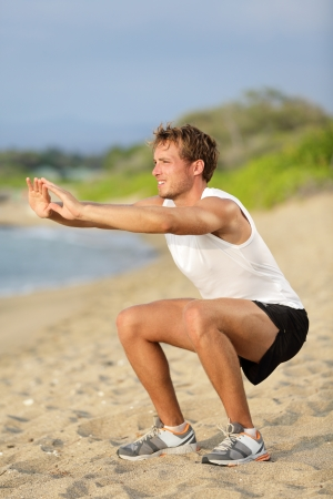 squat: Fitness man training air squat exercise on beach outside