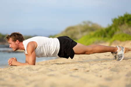 planking: Crossfit training fitness man doing plank core exercise working out his midsection core muscles