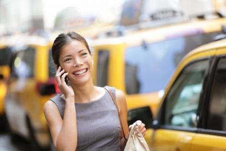 taxi: Mujer de negocios en el teléfono inteligente caminando en traje de vestir bolsa para el perro celebración sonriendo y riendo Foto de archivo