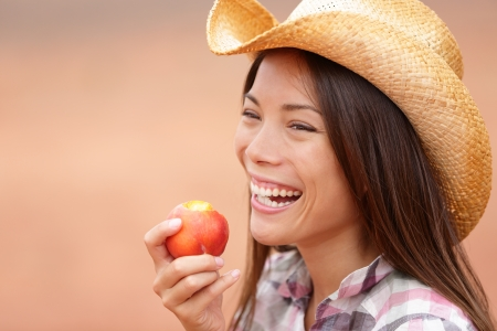 American cowgirl eating peach or nectarine fruit smiling and laughing wearing cowboy hat outside photo