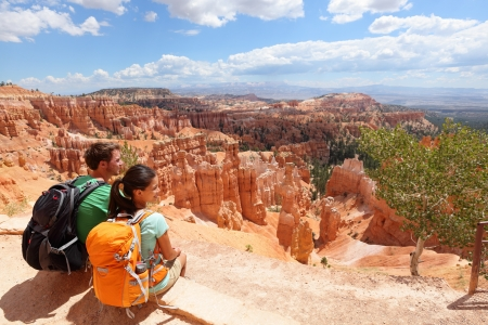 woman hiking: Hikers in Bryce Canyon resting enjoying view Hiking couple in beautiful nature landscape with hoodoos, pinnacles and spires rock formations Stock Photo