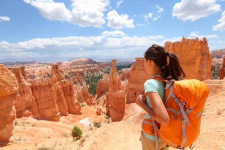 bryce canyon: Hiker woman in Bryce Canyon hiking looking and enjoying view during her hike wearing hikers backpack
