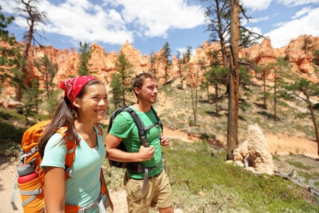 Multiracial couple, young Asian woman and Caucasian man in Bryce Canyon National Park landscape, Utah, United States. photo