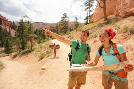 adventure holiday: Young multiracial couple of hikers navigating and smiling happy during hike in Bryce Canyon