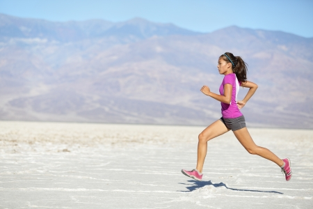 Female sport fitness athlete in high speed sprint in amazing desert landscape outside photo