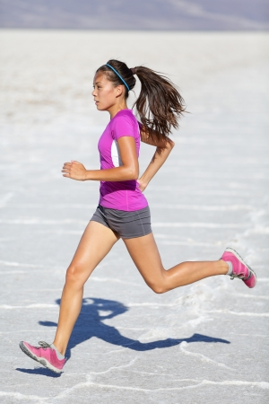 cardio fitness: Running woman - runner sprinting on trail run in desert nature landscape. Female sport fitness athlete in high speed sprint in amazing desert landscape outside. Multiracial fit sports model sprinter.