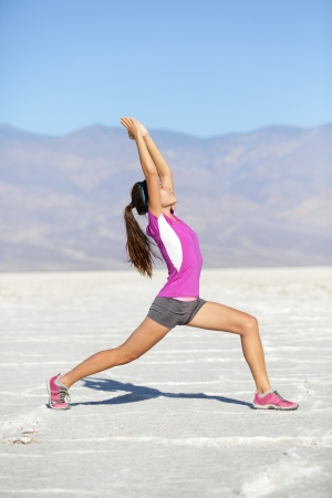 warrior woman: Fitness yoga woman stretching warrior one pose in desert death valley landscape