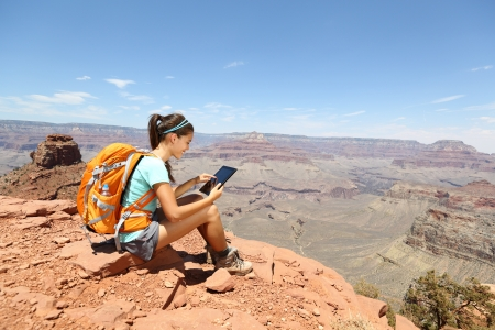 traveller: Tablet computer woman hiking in Grand Canyon using travel app or map during her hike. Multiethnic hiker girl relaxing on South Kaibab Trail, south rim of Grand Canyon, Arizona, USA.