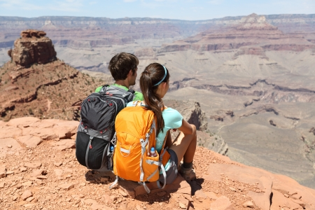 Hikers in Grand Canyon enjoying view of nature landscape. Young couple hiking relaxing during hike on South Kaibab Trail, south rim of Grand Canyon, Arizona, USA. photo