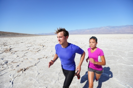 Trail running marathon athletes outdoors in desert. Extreme runners training for fitness and healthy lifestyle outside in dramatic landscape. Asian woman fitness model and fit caucasian athlete. photo
