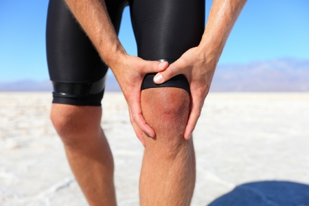 knee joint: Injuries - sports running knee injury on man. Male runner with pain, maybe from sprain knee. Close up of legs, muscle and knee outdoors. Stock Photo