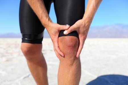 dolor muscular: Lesiones - corriendo lesi�n en la rodilla en el hombre de los deportes. Corredor masculino con el dolor, tal vez de esguince de rodilla. Cerca de las piernas, los m�sculos y la rodilla al aire libre.
