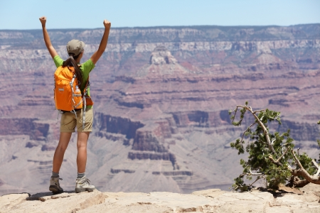 kaibab trail: Grand Canyon hiking woman hiker happy and cheerful with arms raised up outstretched in joy. Winner and success concept with excited elated female hiker outdoors in Grand Canyon, Arizona, USA.