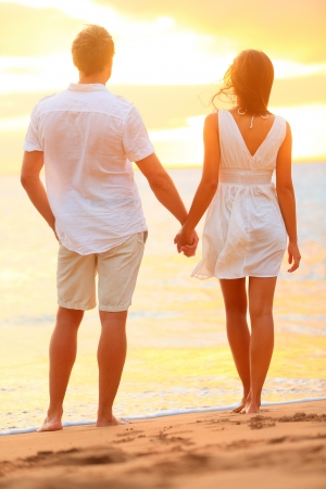 젊은 부부는 로맨스와 태양을 즐기는 해변 일몰에 손을 잡고. 로맨틱 한 여름 휴가 휴가에 사랑에 젊은 행복 한 커플. 캐주얼 의류에 젊은 연인. 아시아