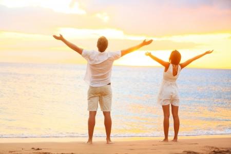 glädje: Lyckliga jublande par njuta solnedgången på stranden med armarna upp i glad upprymd glädje. Lycka koncept med unga glada par, kaukasisk man och asiatisk kvinna. Stockfoto