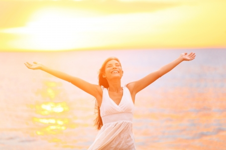 Freedom woman happy and free open arms on beach at sunny sunset. Beautiful joyful elated woman looking up smiling by the ocean during summer holidays vacation. Pretty multiracial Asian Caucasian girl. Stock Photo - 19387053